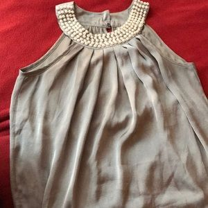 Sleeveless silver top with pearl neck